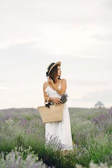 Mujer provenzal relajante en campo de lavanda. dama con un vestido blanco. chica con bolso.