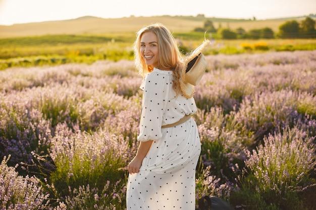 Mujer provenzal relajante en campo de lavanda. dama con un vestido blanco. chica con sombrero de paja.