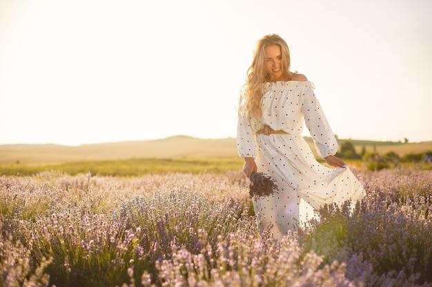 Mujer provenzal relajante en campo de lavanda. dama con un vestido blanco. niña con bouquete de flores.