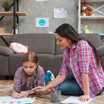 Mujer psicóloga ayudando a niña a dibujar el dibujo en papel.