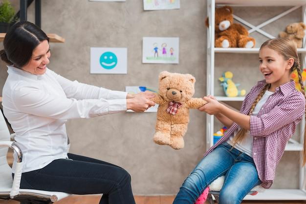 Mujer psicóloga y niña sonriente sentados cara a cara tirando del osito de peluche