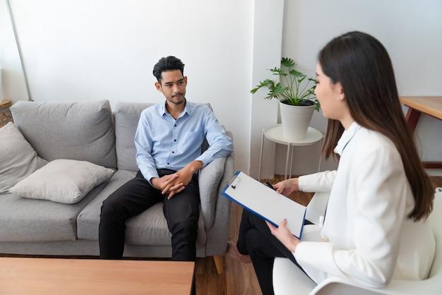 Mujer psiquiatra escribiendo información del paciente joven asiático mientras habla sobre su enfermedad