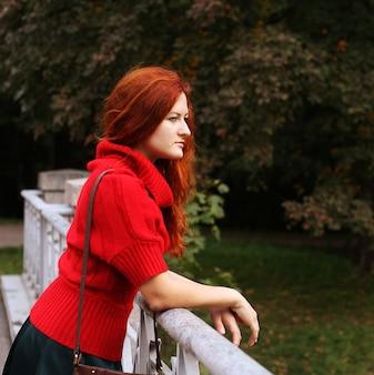 Mujer en puente en el parque otoño