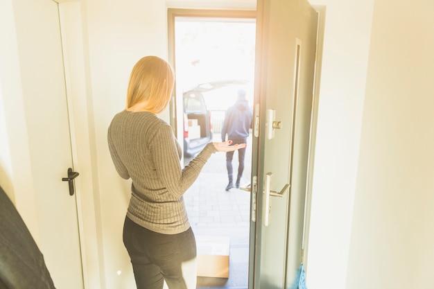 Mujer en la puerta que tiene correo