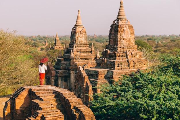 Mujer en la puesta del sol mirando las pagodas budistas