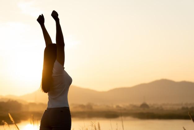 Mujer con el puño en el aire durante el concepto de puesta de sol, libertad, fuerza y coraje.