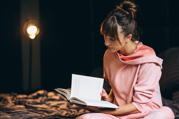 Mujer en pygama sentada en la cama y leyendo un libro