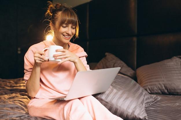 Mujer en pygama trabajando en laptop en cama