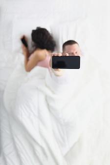 La mujer que se aleja oculta la pantalla del teléfono inteligente de su esposo mientras está acostado en la cama, el esposo la mira usando la aplicación de su teléfono inteligente