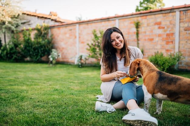Mujer que alimenta el perro de perrito lindo del beagle de la mano.