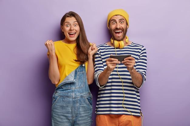 Mujer que anima feliz se regocija, un hombre sostiene el smartphone horizontalmente