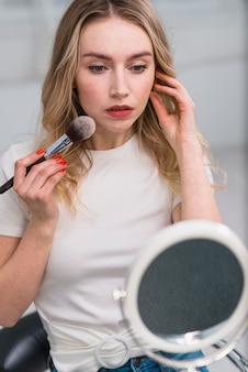 Mujer que aplica el colorete que mira en espejo