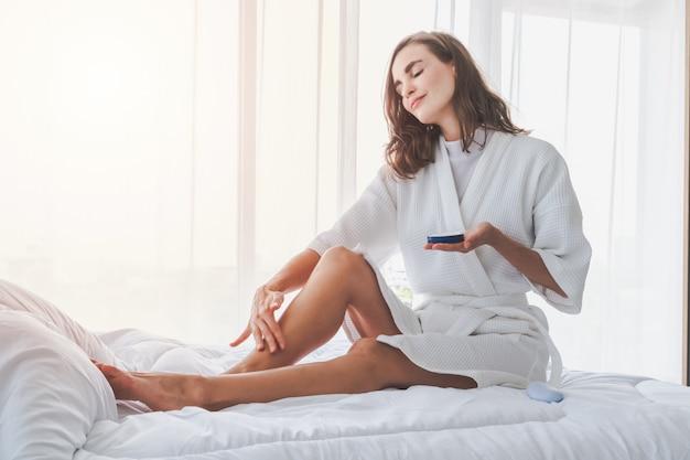 Mujer que aplica crema o loción corporal refrescante en sus piernas y mano