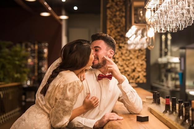 Mujer que besa al hombre feliz en el contador de la barra