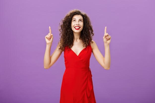 La mujer que va a la calle, respira aire fresco y disfruta de los fuegos artificiales en su honor, mirando y apuntando hacia arriba con una expresión de ensueño y alegría, sonriendo alegremente de pie sobre un fondo púrpura en un vestido de noche rojo.