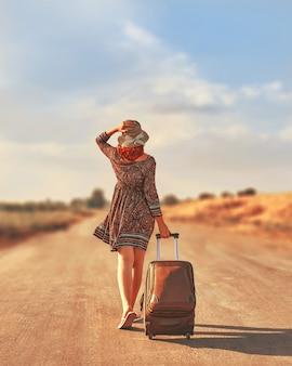 Mujer que camina en el camino con equipaje. concepto de libertad
