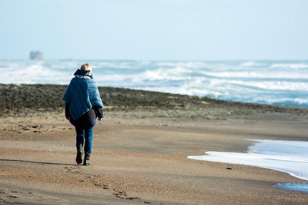 Mujer que camina por la orilla del mar en invierno.
