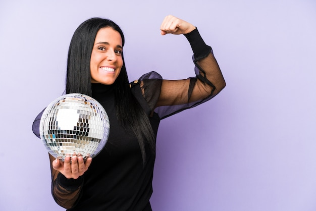 Mujer que celebra una fiesta de la bola aislada en el puño de levantamiento púrpura después de una victoria, concepto del ganador.