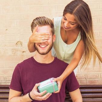 Mujer que cierra los ojos de su novio que da el regalo sorpresa