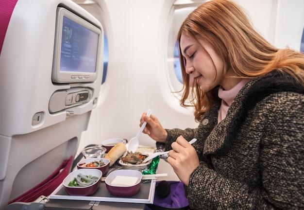 Mujer que come la comida en el aeroplano comercial en tiempo de vuelo.