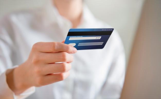 La mujer que compra en línea y retiene la vista de la tarjeta de crédito ingresa el código de pago del producto.