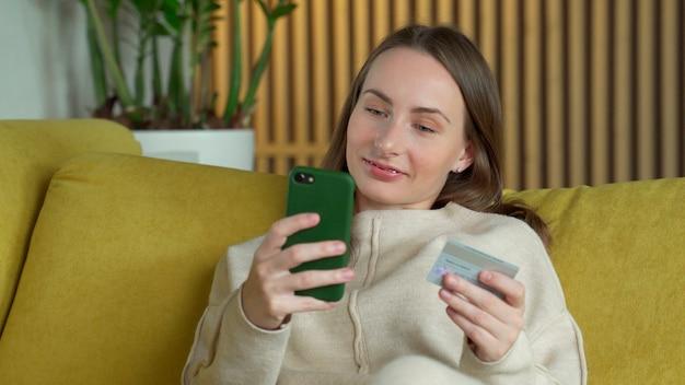 Mujer que compra en línea con una tarjeta de crédito y un teléfono inteligente sentado en un sofá amarillo en casa
