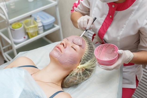 Mujer que consigue la máscara de peeling facial en el salón de belleza spa