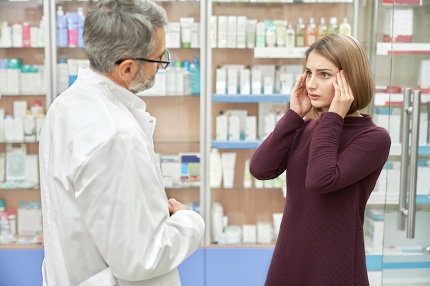 Mujer que consulta con el farmacéutico sobre dolor de cabeza.