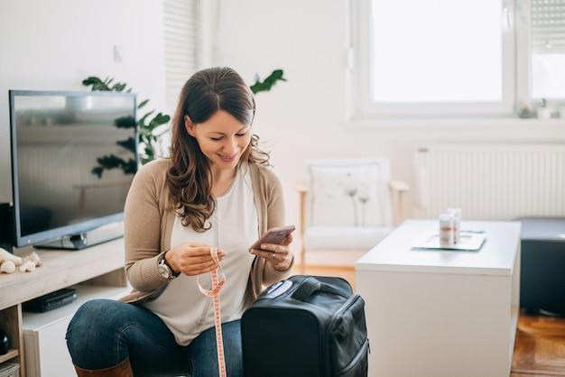 Mujer que controla los requisitos de tamaño de equipaje del aeropuerto de teléfono.