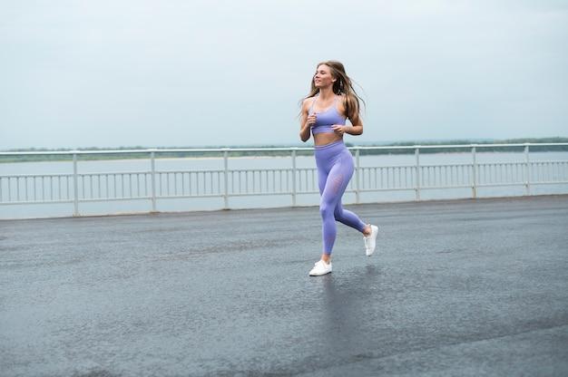Mujer que corre a lo largo del lago tiro largo