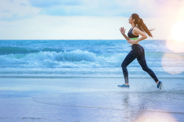 Mujer que corre en la playa con puesta del sol.