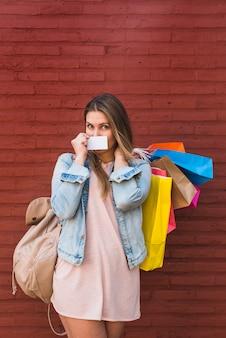 Mujer que cubre la boca con tarjeta de crédito