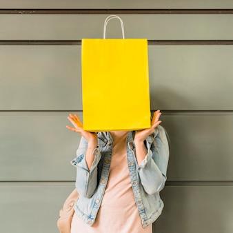 Mujer que cubre la cara con el bolso de compras amarillo
