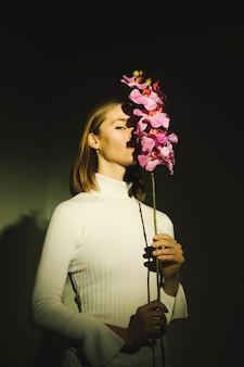 Mujer que cubre la cara con la flor brillante