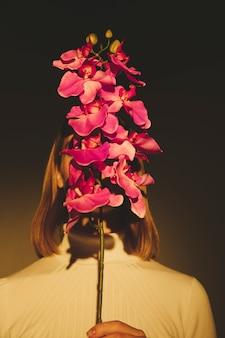 Mujer que cubre la cara con la flor