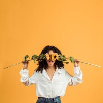 Mujer que cubre la cara con flores