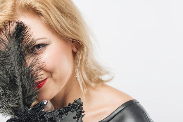 Mujer que cubre la cara con plumas de máscara negra.