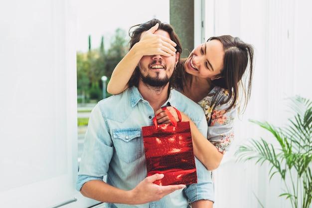 Mujer que cubre los ojos del hombre con bolsa de regalo