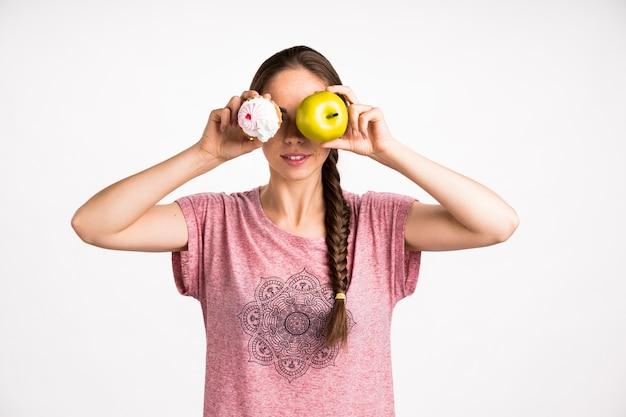 Mujer que cubre su rostro con cupcake y manzana