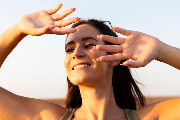 Mujer que cubre su rostro del sol mientras está al aire libre