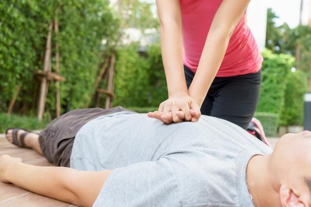 Mujer que da la reanimación cardiopulmonar (cpr) a un hombre en el parque público.