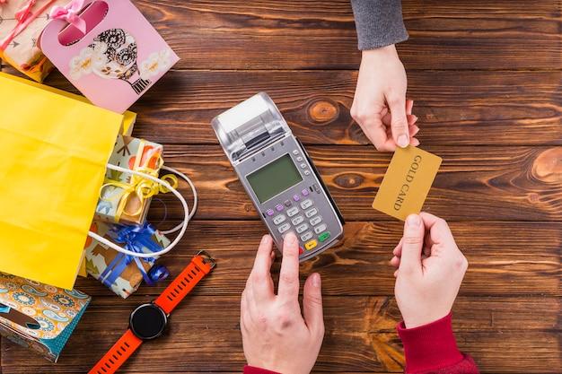 Mujer que da la tarjeta bancaria al dependiente para el pago