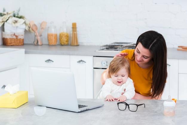 Mujer que detiene al bebé en la cocina con la computadora portátil