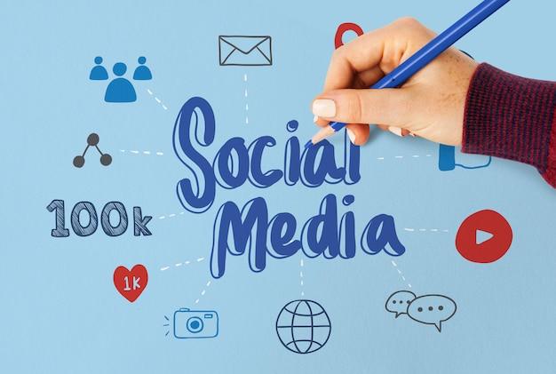 Mujer que dibuja plan de medios sociales en un papel azul