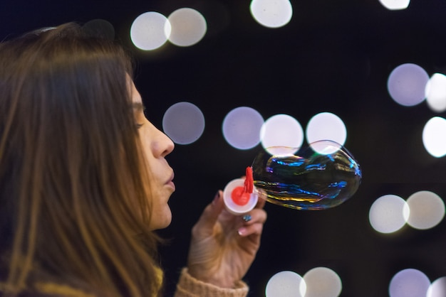 Mujer que se divierte haciendo pompas de jabón en la fiesta de la noche o la celebración de año nuevo