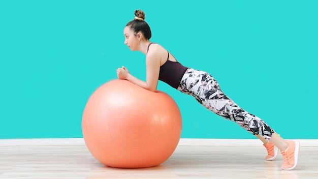Mujer que ejercita en bola apta