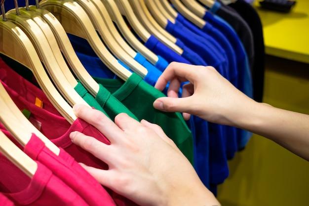 Mujer que elige la camiseta colorida de moda