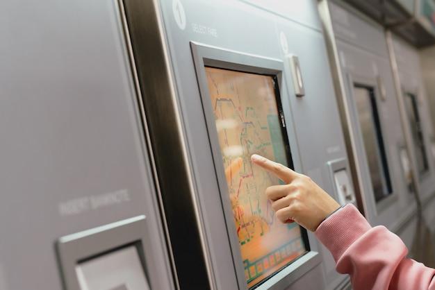 Mujer que elige el destino en la máquina del boleto del metro.