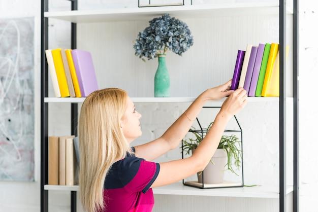 Mujer que elige un libro del estante en casa