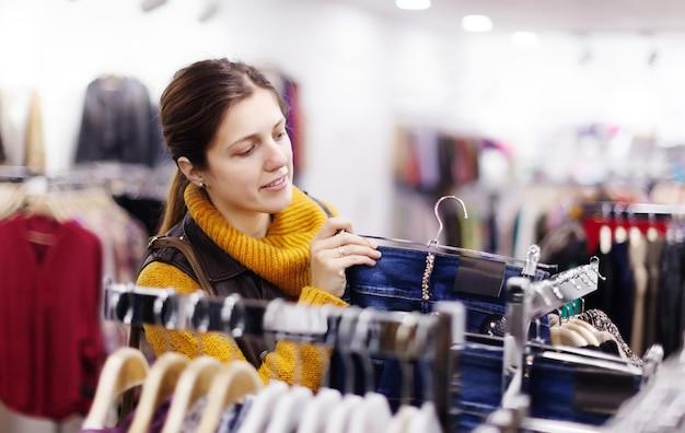 Mujer que elige los pantalones vaqueros en la tienda